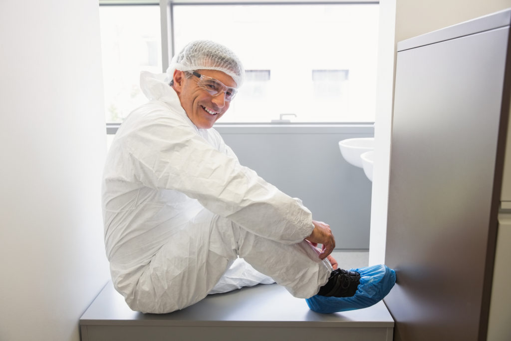 Pharmacist putting on his shoe covers at the laboratory